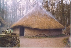 """Recreated Celtic Village, Museum of Welsh Life. The open fire within the circular hut gives the thatched roof a """"steaming"""" effect. Three round wattle-and-daub huts are surrounded by a ditch and wooden palisade. (Source: Wikimedia Commons)"""